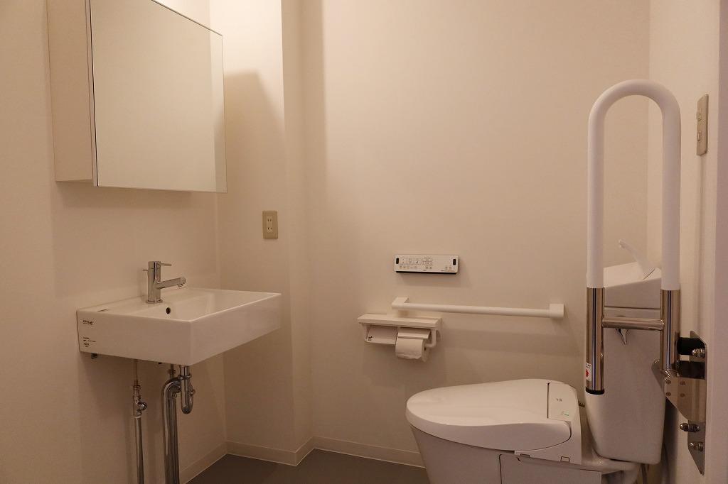手すりを設け、広く作られたトイレ。一般的には入口側に向けて便器が置かれるが、それだと介助者と目が合いやすい。それを避けるための配置だという