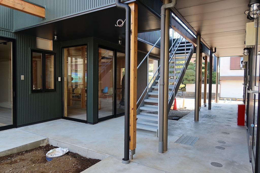 2棟を繋ぐ階段、廊下スペースから入口方向を見たところ。出入りには顔を合わせる作りになっている