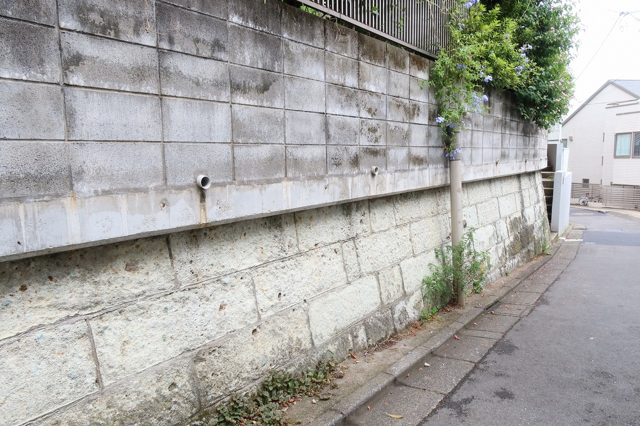劣化した大谷石の上に擁壁としては向かないコンクリートブロックを積んだもの。異なる素材を重ねるのはどうなのか